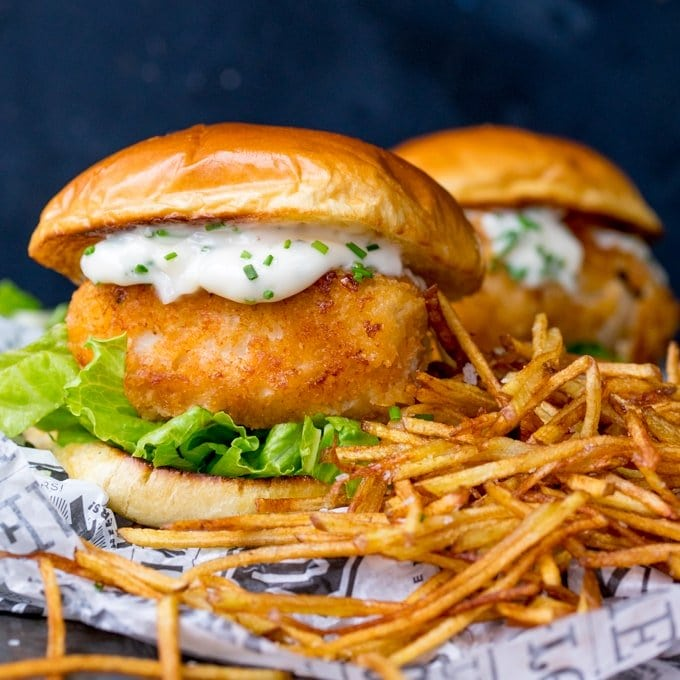 Breaded haddock burger on brioche bun with lettuce and chive-speckled mayonnaise. Shoestring fries to the right of the burger. A second burger in background.