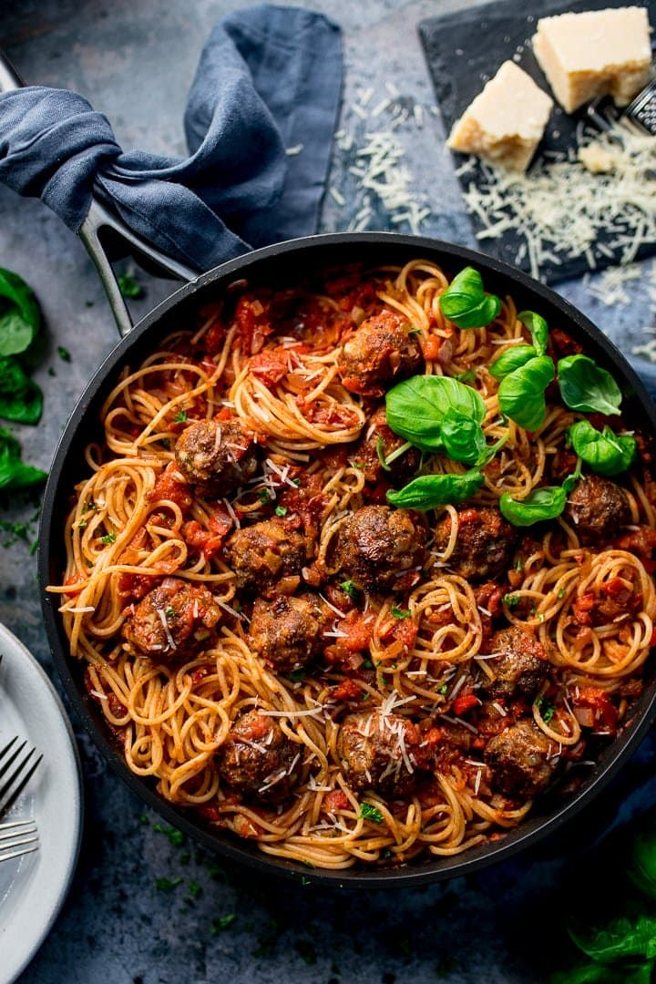 Spaghetti and meatballs in a pan on a blue background