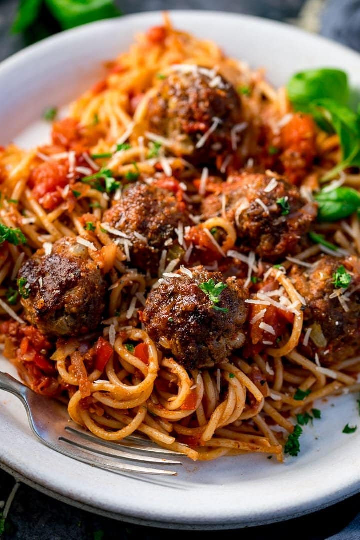 Meatballs and spaghetti on a white plate with basil and parsley