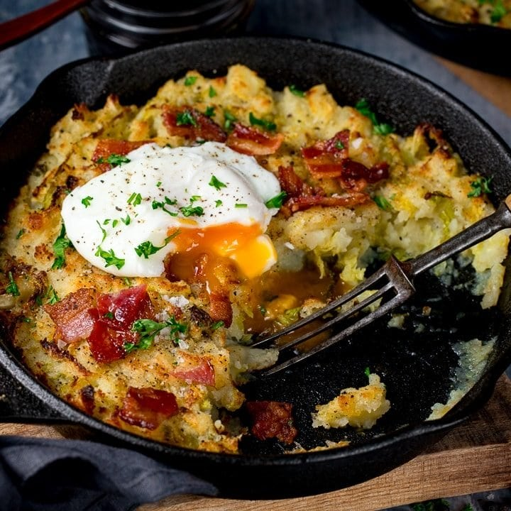 bubble and squeak in a pan with a portion taken out. Running poached egg on top