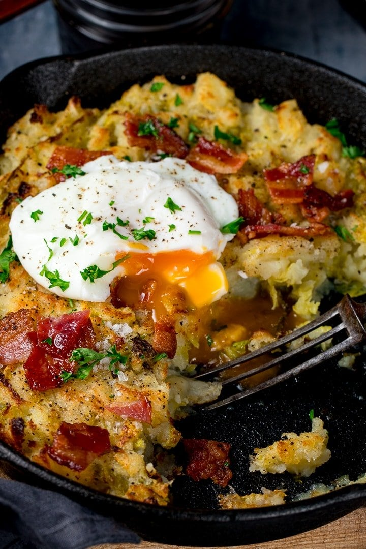 Close up of runny poached egg on top of bubble and squeak in a pan