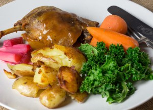 Duck confit with roast potatoes, carrots and kale on a white plate.