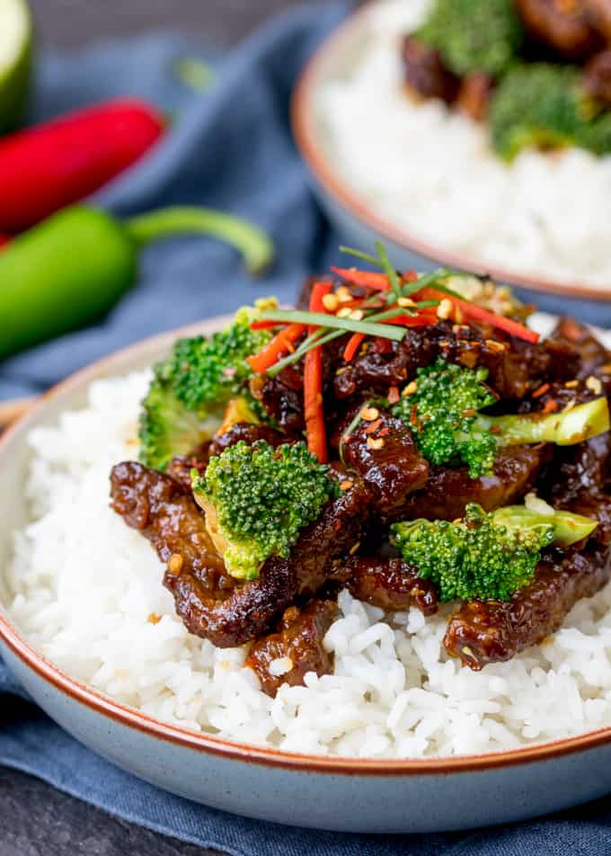 Crispy beef strips and broccoli in a tangy sauce on top of a bowl of boiled rice. Further bowl in the background.