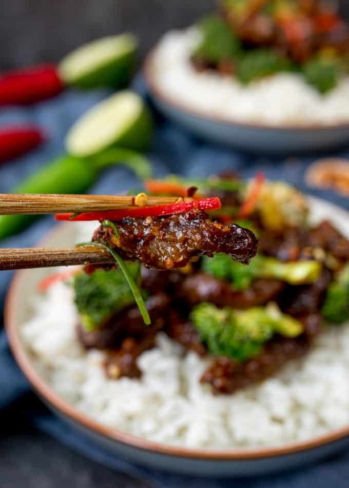 Chopsticks taking a piece of beef from a bowl of crispy beef and broccoli with rice