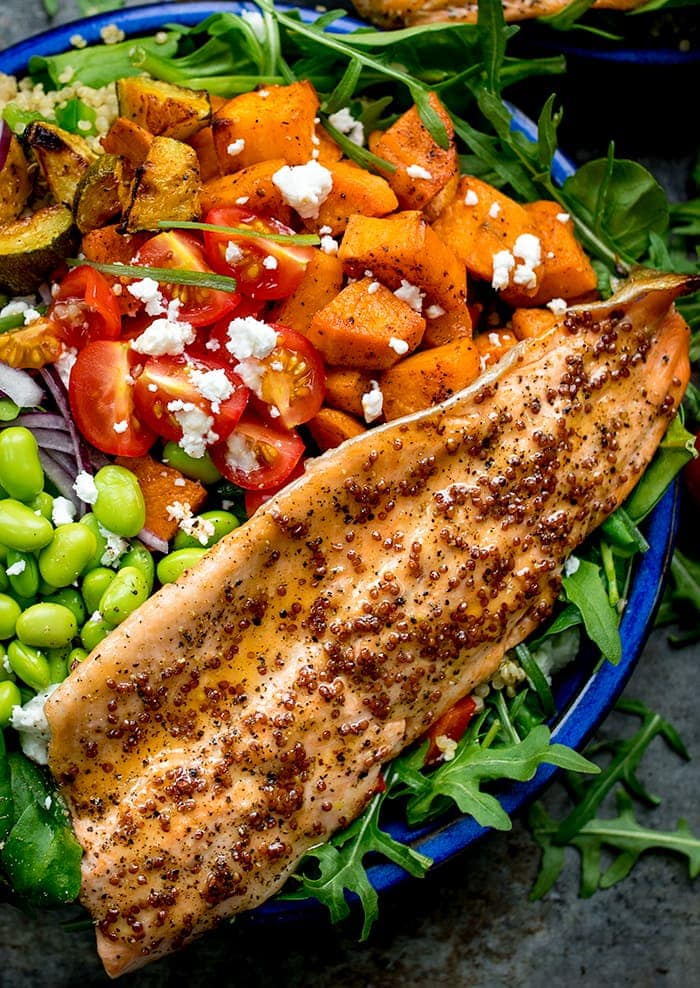 Close up image of salad bowl filled with roasted veg, tomatoes, edamame, red onion, courgette and topped with honey mustard trout.