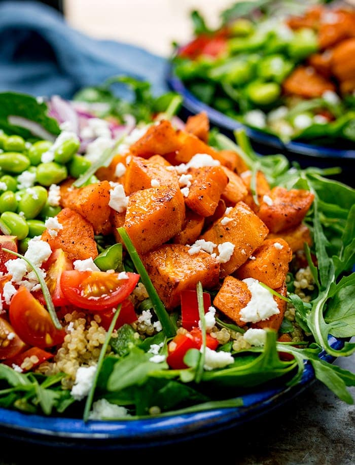 Close up of a bowl of salad with roasted sweet potato, edamame, tomato, quinoa and feta