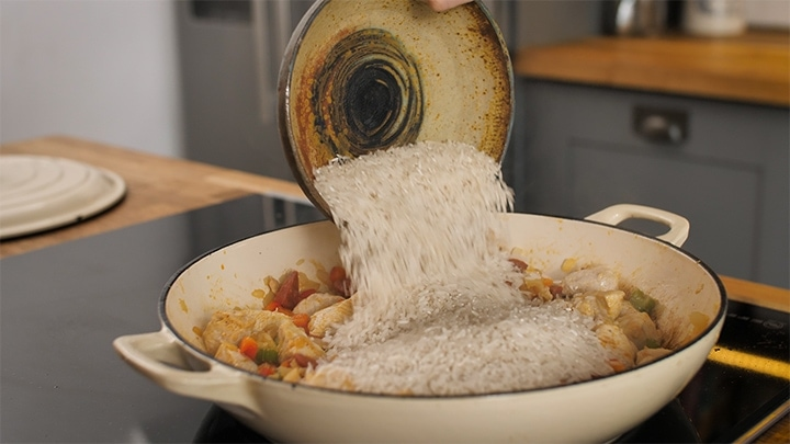 Rice being poured into a pan of chicken and chorizo for jambalaya