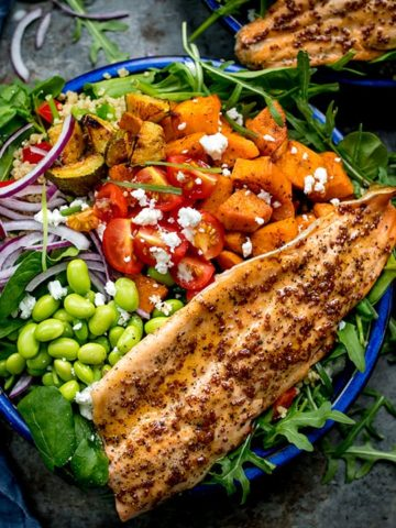 Salad bowl filled with roasted veg, tomatoes, edamame, red onion, courgette and topped with honey mustard trout.