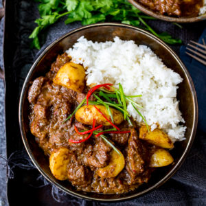 Bowl of beef massaman curry with rice on a dark background