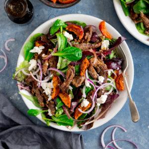 Platter of crispy lamb, tomato and feta salad.