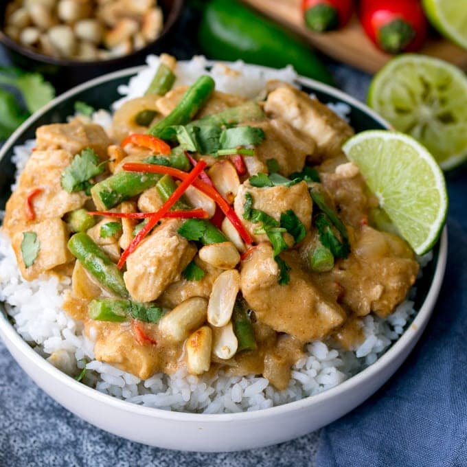 Bowl of rice topped with peanut butter chicken with green beans, chillies and coriander (cilantro)