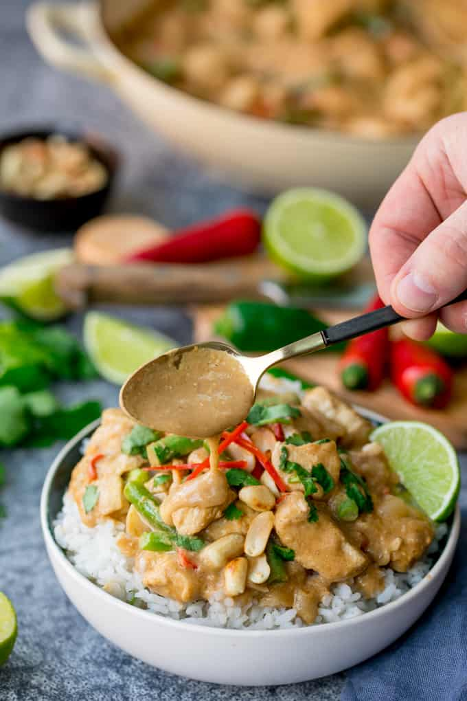 Bowl of rice topped with peanut butter chicken with green beans, chillies and coriander (cilantro). Extra sauce being spooned on top.
