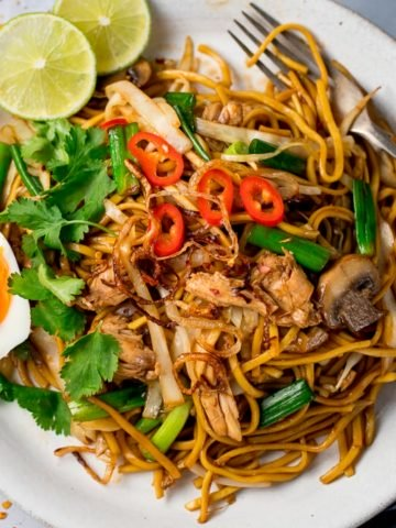 overhead of a Mee goreng (asian noodles) on a white plate with egg, chillies and lime slices