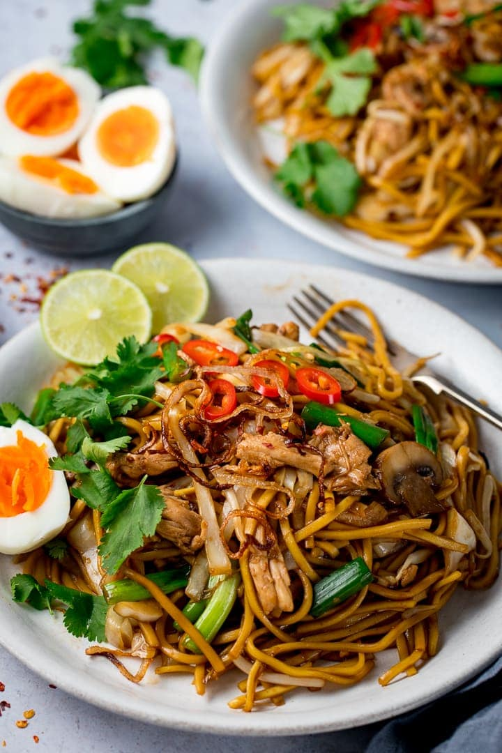Mee Goreng (asian noodles) on a white plate with hard boiled egg, crispy onions and sliced red chillies