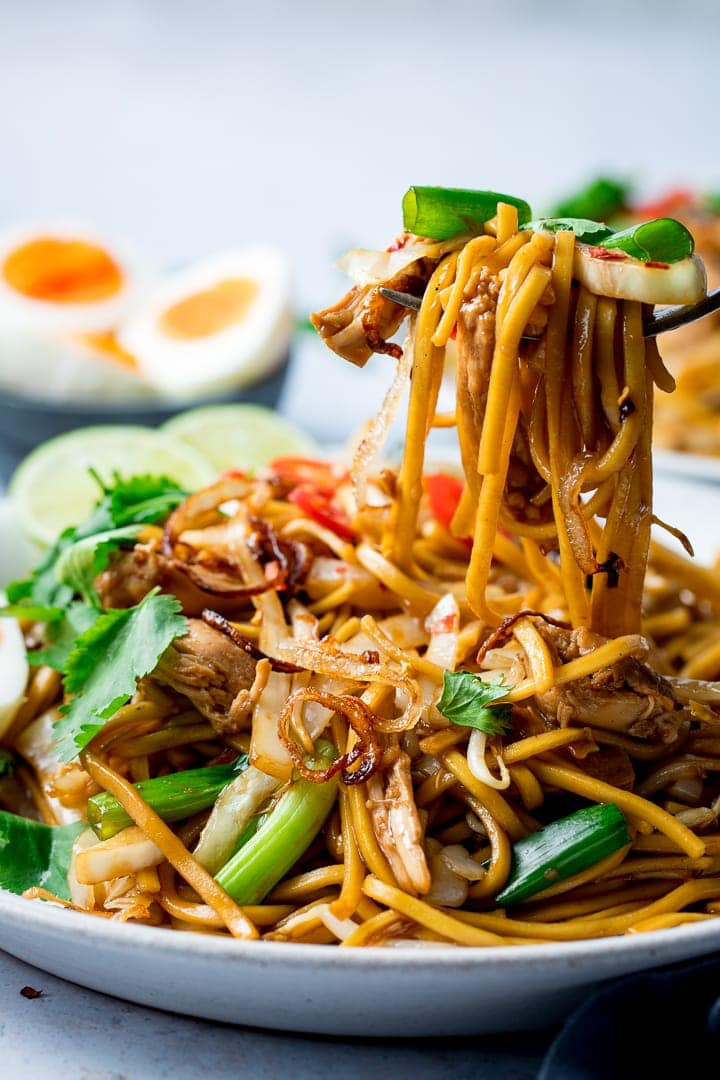 Mee goreng on a plate being lifted with a fork