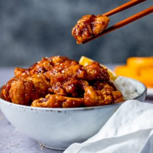 Piece of orange chicken being lifted from a bowl using chopsticks