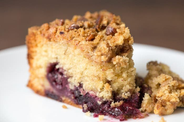 Close up picture of Cherry Crumble Cake showing the layer of cherries , the crispy crumble top and the fluffy cake texture