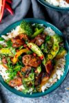 Chicken stir fry with vegetables on rice in a green bowl