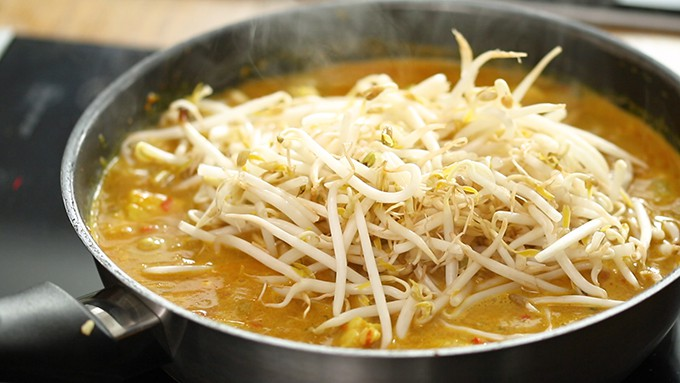 Close up of Laksa curry sauce in a frying pan with fresh beansprouts on top.