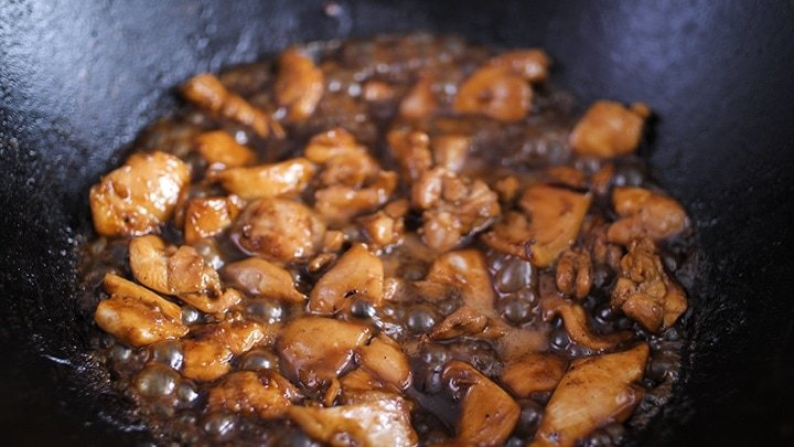Marinated chicken cooking in a wok