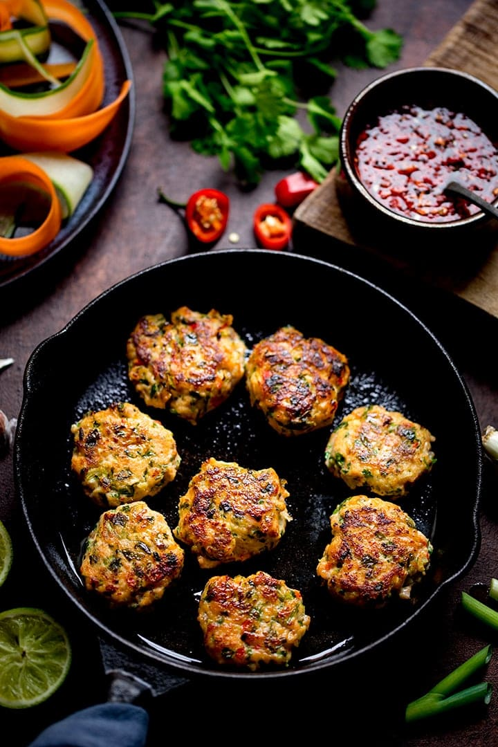 Thai Fishcake Bites in a pan with ingredients scattered around