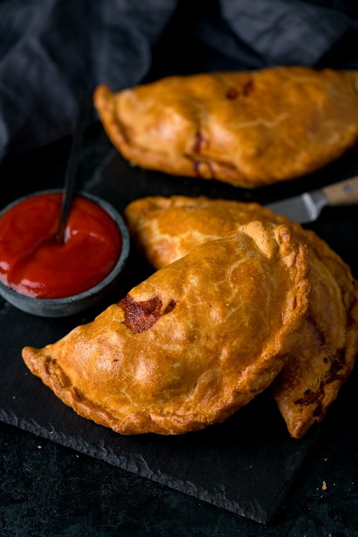 Cornish pasties on a dark serving board with ketchup next to them