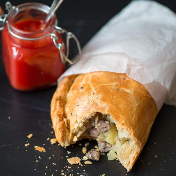 A Cornish Pasty, wrapped in grease proof paper with a bite taken our and a jar of tomato ketchup in the background