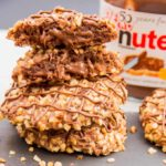 Gluten Free Hazelnut Nutella Cookies - Soft oat flour chocolate biscuits, rolled in hazelnuts and filled with a gooey chocolate centre.