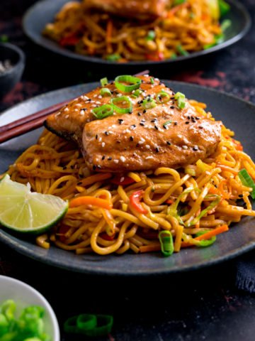 Square image of Asian salmon on top of stir fried noodles on a dark blue plate. Further plate of salmon and noodles in the background along with little plates of garnishes.