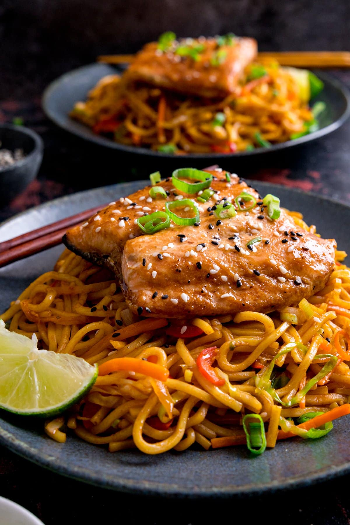 Asian salmon topped with spring onions on a bed of stir-fried noodles on a blue plate. Further plate with salmon and noodles in the background.