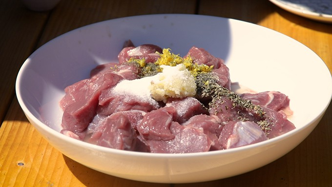 chunks of lamb in a bowl with garlic, lemon and herb marinade.