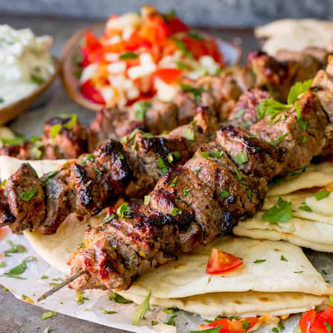 Square image of Lamb souvlaki kebabs on top of toasted breads