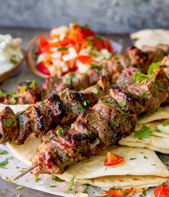 Lamb souvlaki kebabs on top of toasted breads with tomato and onion salad in background