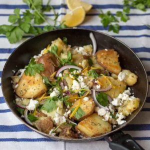 Pan of Greek potatoes with feta, red onion and parsley on a blue and white striped tea towel