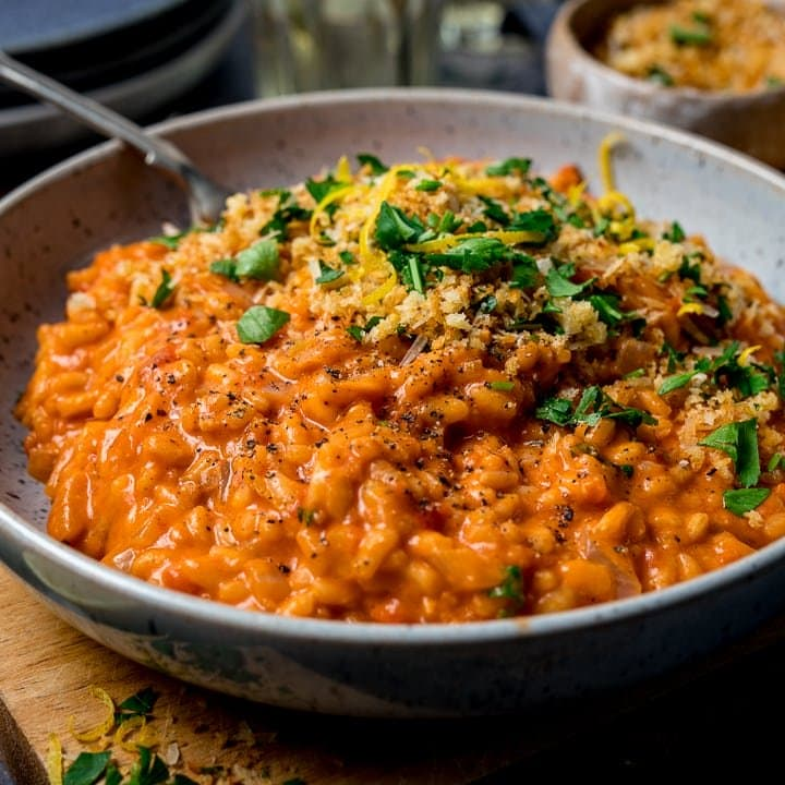 Bowl of creamy tomato risotto topped with crispy crumbs and parsley