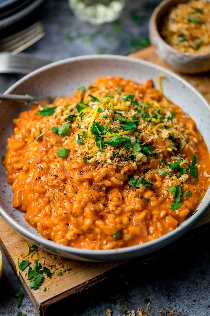 Bowl of tomato risotto on a wooden board