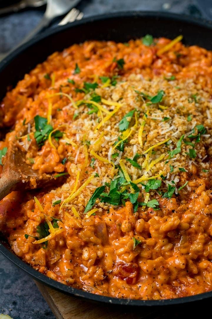 Pan of tomato risotto topped with crispy crumbs, parsley and lemon zest