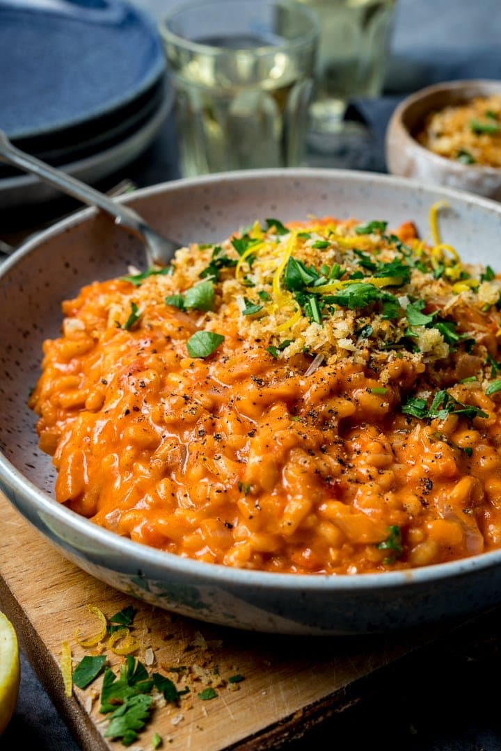 Blue bowl filled with tomato risotto and topped with crispy garlic crumbs