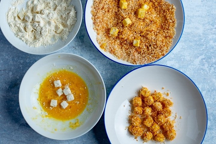 Cubes of feta being floured, dipped in egg and breadcrumbs