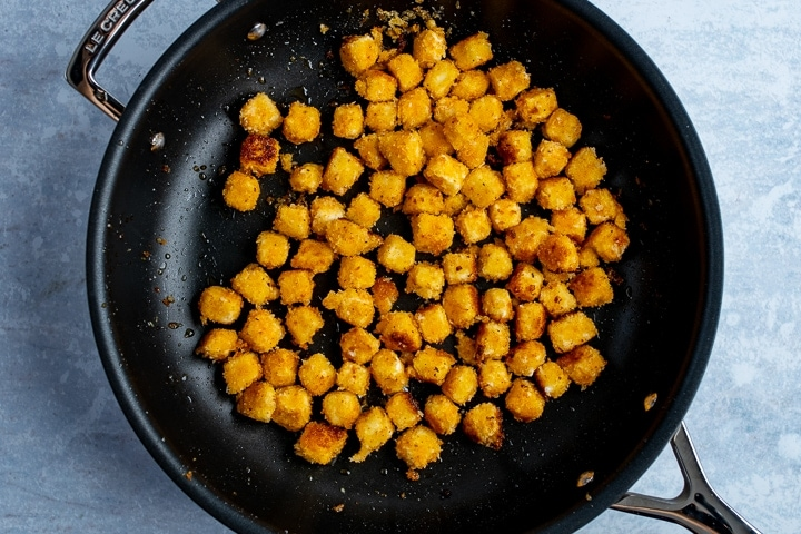 Coated feta cubes being fried in a pan