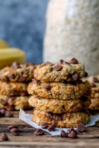 Pile of banana oat chocolate chip cookies on a wooden background.