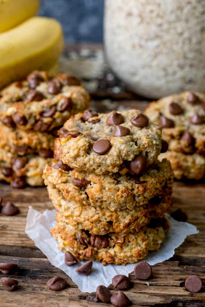 Tall image of a pile of banana chocolate chip oat cookies