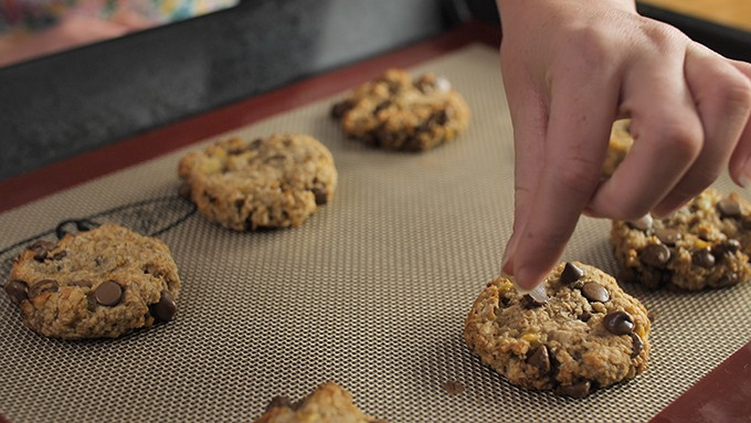 Adding extra chocolate chips to warm banana oat cookies.