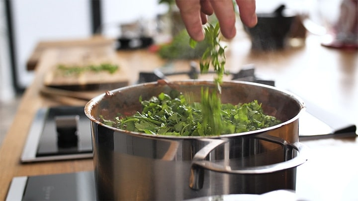 Coriander being sprinkled into a pan of chilli con carne