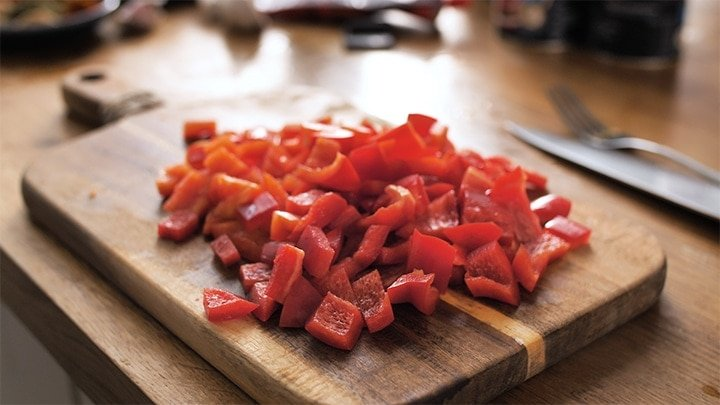 Chopping board with chopped red bell peppers on