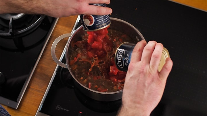 Tinned tomatoes being added to a pan of chilli con carne