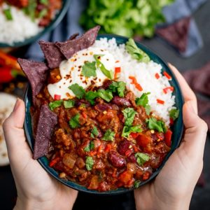 Hands holding bowl of Bowl of chilli con carne with rice