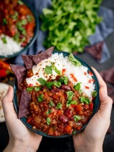 Hands holding bowl of Bowl of chilli con carne with rice and blue corn chips