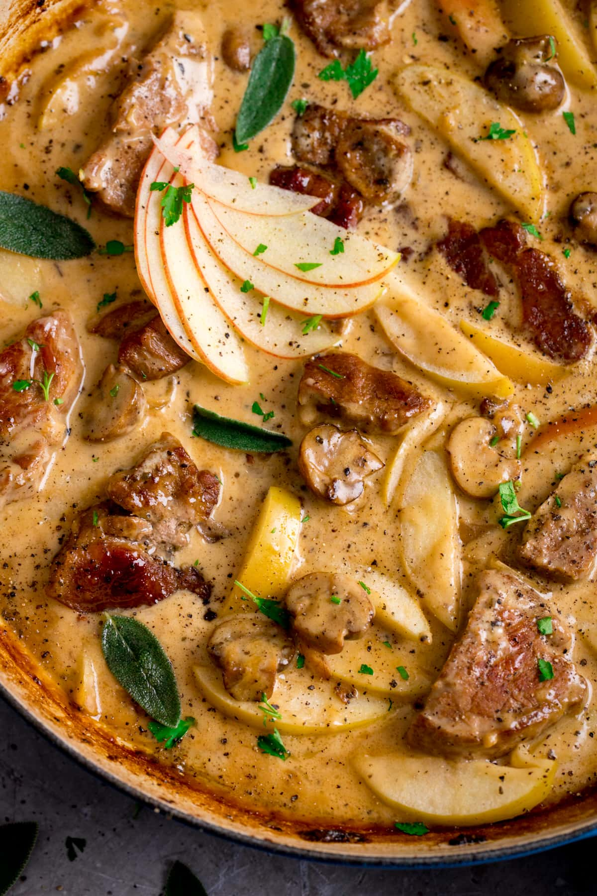 Close up overhead shot of creamy pork and apple casserole in a casserole dish.