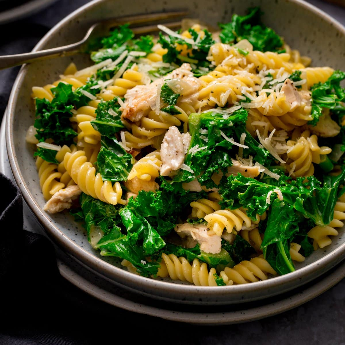 Close up of a bowl of garlic chicken pasta and kale with a fork in the bowl.